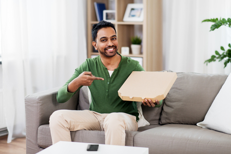 indian man with box of takeaway pizza at home