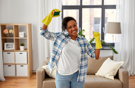 happy african woman with sponge cleaning at home