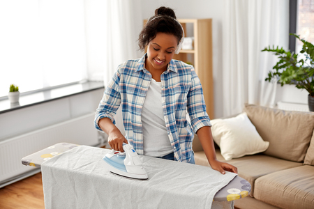 african american woman ironing bed linen at home 版權商用圖片