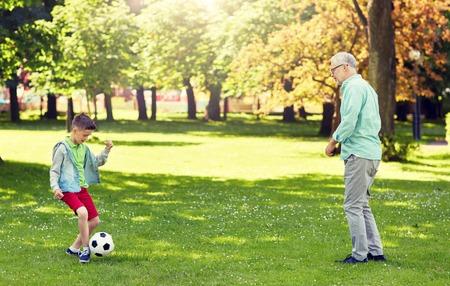 alter Mann und Junge, die Fußball im Sommerpark spielen