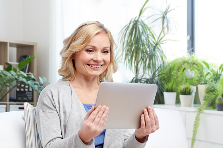 middle aged woman with tablet computer at home