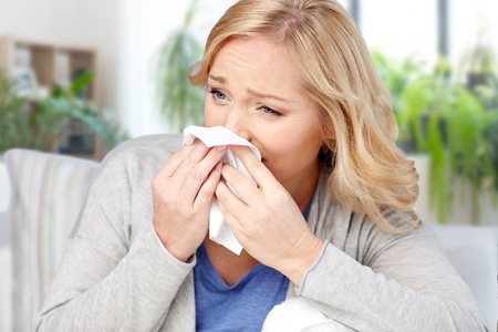 ill woman blowing nose to tissue at home