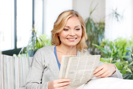 smiling woman reading newspaper at home 写真素材