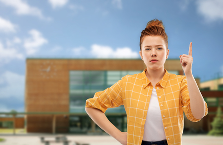 red haired teenage girl with finger up over school