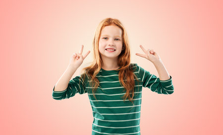 smiling red haired girl showing peace gesture Stockfoto
