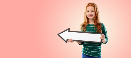 smiling red haired girl with arrow showing to left Stockfoto