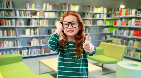 red haired student girl in glasses at library