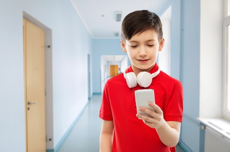 boy in red t-shirt with headphones and smartphone