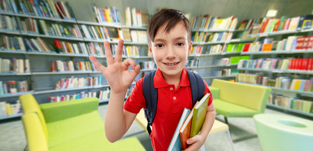 student boy with books showing ok at library