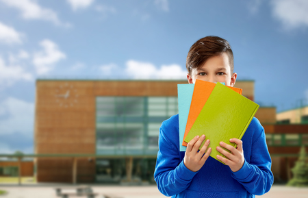 shy student boy hiding behind books over school