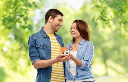 smiling couple holding house model
