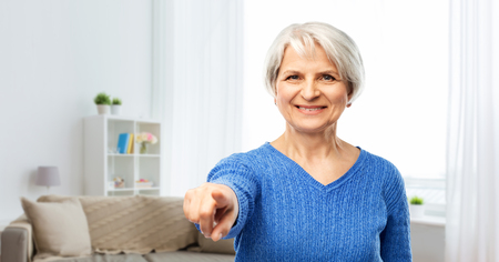 happy senior woman pointing finger to you at home Stock Photo