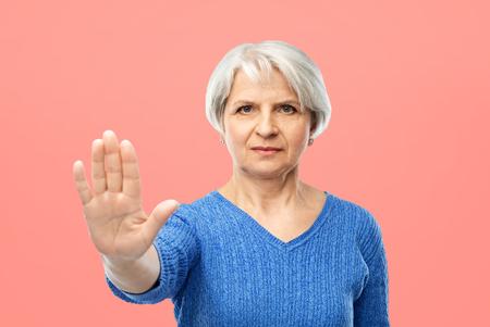 senior woman in blue sweater making stop gesture