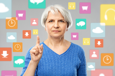 senior woman pointing finger up over app icons