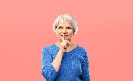 senior woman making shush gesture over pink