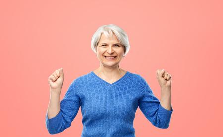 portrait of happy senior woman celebrating success