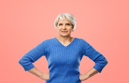 senior woman in blue sweater hands on hips