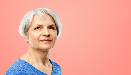 portrait of senior woman in blue sweater over pink