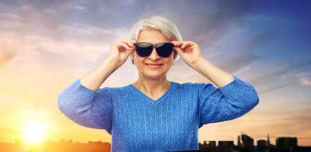 senior woman in sunglasses over sunset in city Banco de Imagens