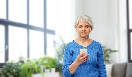 senior woman using smartphone at home