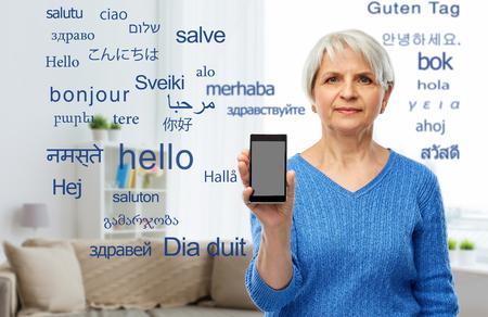senior woman using translator on smartphone
