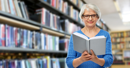 senior woman in glasses reading book at library