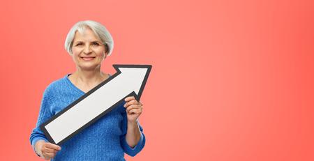 smiling senior woman with big rightwards arrow