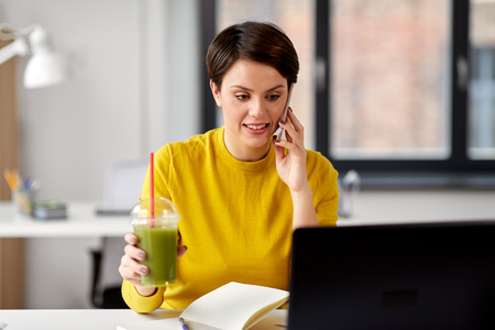 woman with drink calling on smartphone at office