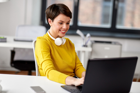 happy businesswoman with laptop working at office
