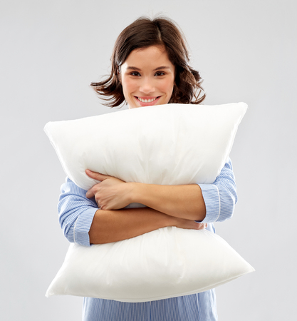 happy young woman in pajama hugging pillow Imagens