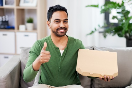 indian man with takeaway pizza showing thumbs up Stock Photo