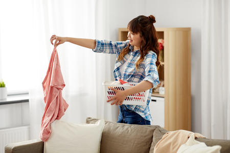 asian woman picking dirty laundry at home