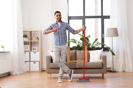 smiling indian man with broom cleaning at home