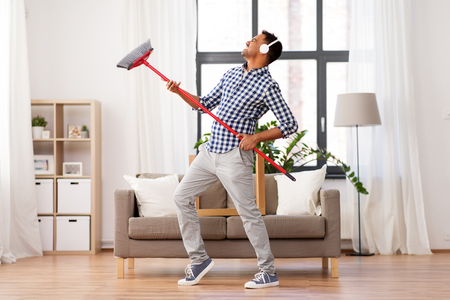 man with broom cleaning and having fun at home Reklamní fotografie
