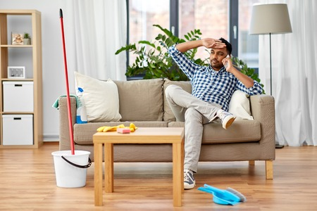 man calling on smartphone after cleaning home Stock Photo