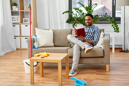 man reading book and resting after home cleaning