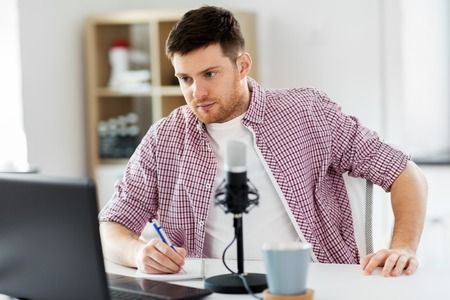 audio blogger with laptop, microphone and notebook