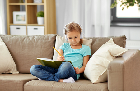 girl in headphones with diary on sofa at home