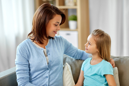 mother and daughter looking at each other at home Stock Photo