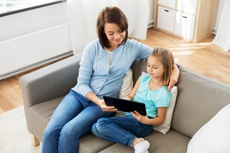 happy mother and daughter with tablet pc at home Stock Photo