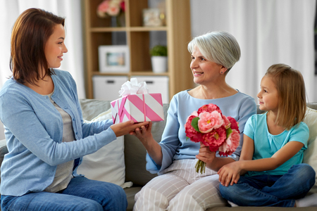 female family giving present to grandmother