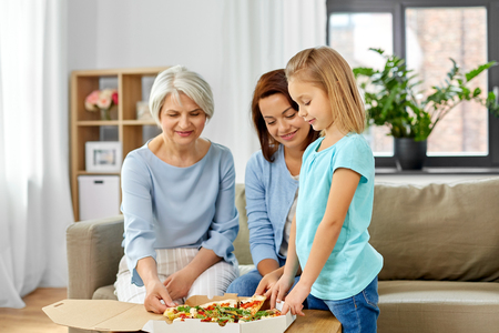 mother, daughter and grandmother eating pizza 版權商用圖片 - 124772669