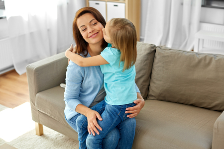 daughter hugging and kissing her mother at home Stock Photo
