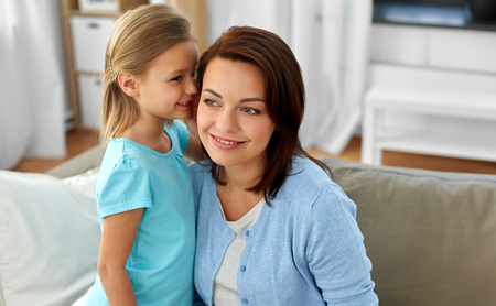 daughter whispering secret to mother at home Stock Photo