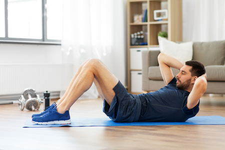 man making abdominal exercises at home