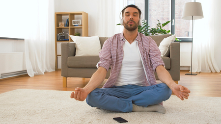 mindfulness, spirituality and music concept - man in headphones meditating in lotus pose at home Stock Photo