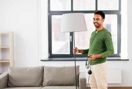 accommodation and interior concept - happy indian man holding floor lamp at home