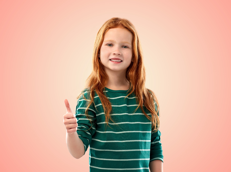 smiling red haired girl showing thumbs up