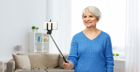 smiling senior woman taking selfie by smartphone