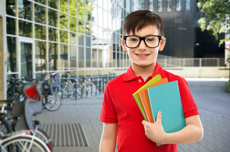 smiling schoolboy in glasses with books